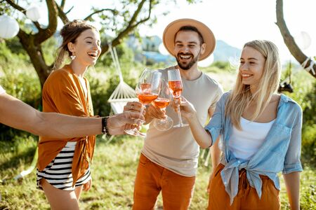 Young and cheerful friends having fun, clinking with wine glasses in the beautifully decorated backyard during a festive meeting or party on a sunny summer evening Stock Photo