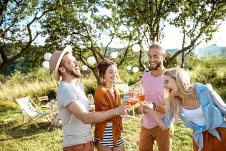 Young and cheerful friends having fun, clinking with vine glasses in the beautifully decorated backyard during a festive meeting or party on a sunny summer evening