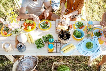人们在庭院里度过节日午餐用健康食品在美妙地装饰的桌子上,顶视图