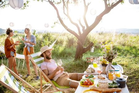 Group of a young friends having festive lunch in the beautifully decorated garden with table full of healthy food on a sunset Stock Photo - 128769393