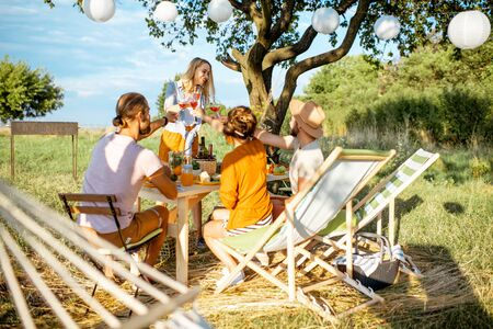 Young people having festive lunch in the beautifully decorated garden with hammock and garland on a summer afternoon Stock Photo - 128769404