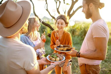 Group of a happy friends having fun, eating food and drinking wine during a festive lunch in the garden on a sunset
