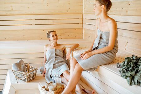 Two young girlfriends wrapped in sheets relaxing in the sauna. Concept of female friendship and spa treatment Stok Fotoğraf