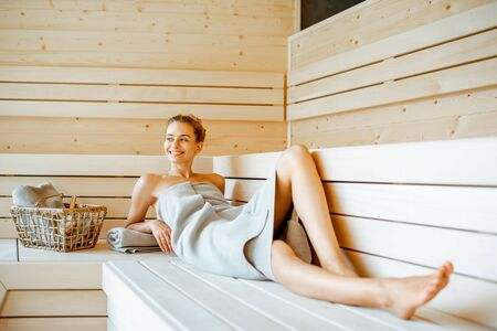 Young beautiful woman wrapped with sheet relaxing in the sauna