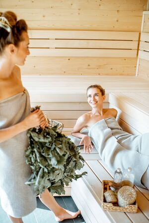 Two young girlfriends relaxing in the sauna, holding bath broom and talking together Banco de Imagens