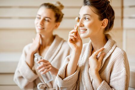 Young women taking care of their skin, making facial massage in the SPA, sitting together in bathrobes Stock fotó