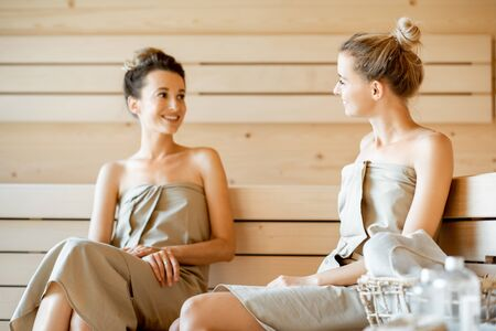 Two young girlfriends having cheerful conversation while relaxing in the sauna. Concept of female friendship and spa treatment