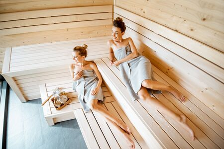 Two young girlfriends relaxing in the sauna, lying on the wooden benches with bucket and bath brooms