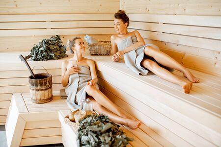 Dwie młode dziewczyny relaksujące się w saunie, leżące na drewnianych ławkach z wiaderkiem i miotłami kąpielowymi