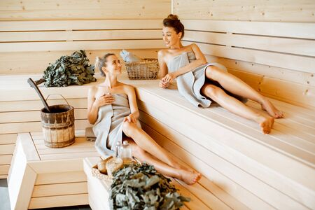 Two young girlfriends relaxing in the sauna, lying on the wooden benches with bucket and bath brooms 免版税图像 - 128770043