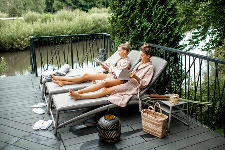 Two young women in bathrobes lying on the sunbeds, relaxing and spending time at the luxury SPA outdoors on the terrace Stock Photo