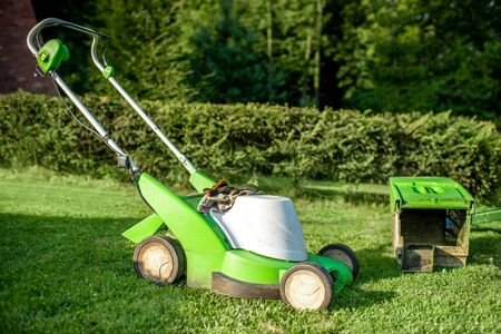 Green lownmower on the grass on the backyard 스톡 콘텐츠