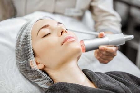 Woman during the oxygen mesotherapy procedure at the beauty salon, close-up view. Concept of a professional facial treatment