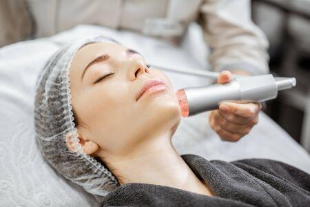 Frau während des Sauerstoffmesotherapieverfahrens im Schönheitssalon, Nahaufnahme. Konzept einer professionellen Gesichtsbehandlung
