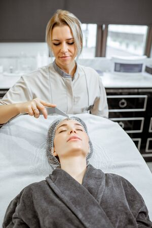 Female cosmetologist making vacuum hydro peeling to a woman at the luxury beauty salon. Concept of a professional facial treatment