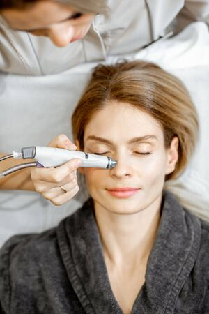 Cosmetologist making vacuum hydro peeling on the nose region to a woman at the luxury beauty salon. Concept of a professional facial treatment Stock Photo