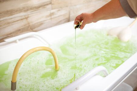 Pouring special ingredient for hydromassage into the tub filled with hot water in the spa