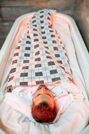 Man lying in the hot SPA capsule wrapped with bedcover during the mud wrap procedure in the SPA salon