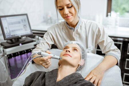 Cosmetologist making vacuum hydro peeling on the cheek area to a woman at the luxury beauty salon. Concept of a professional facial treatment Stok Fotoğraf