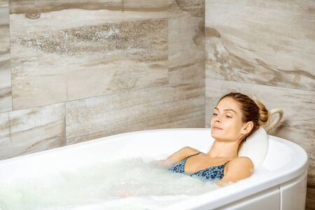 Beautiful woman relaxing in the bathtub having a hydromassage therapy in the SPA