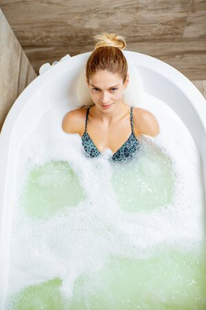 Beautiful woman relaxing in the bathtub having a hydromassage therapy in the SPA. View from above