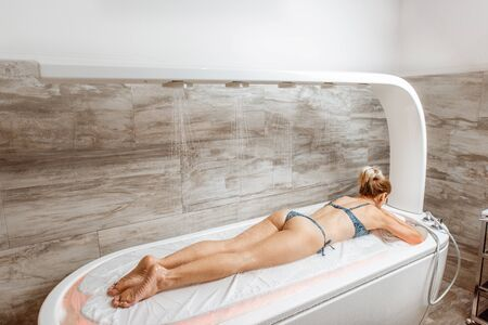 Beautiful woman in swimsuit lying on the wet bed under the hot shower, having a hydromassage in the spa salon Banque d'images
