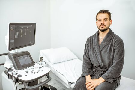 Portrait of a handsome male patient sitting before the ultrasound diagnostics at the medical office. Concept of ultrasound examination of male health