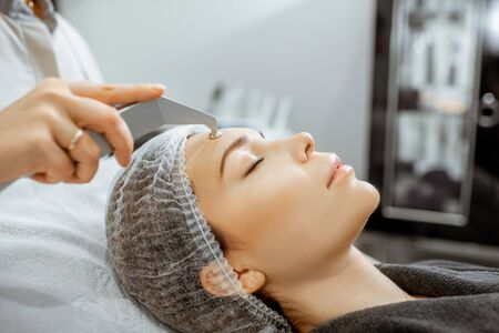 Woman during a vacuum hydro peeling at the luxury beauty salon, close-up view Concept of a professional facial treatment