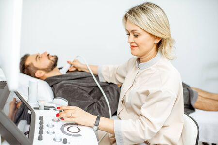 Female doctor performs ultrasound examination of a mens thyroid in the medical office. Concept of ultrasound diagnostics of male health Zdjęcie Seryjne