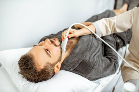 Men examining his thyroid with ultrasound sensor, lying in bathrobe on the couch at the medical office