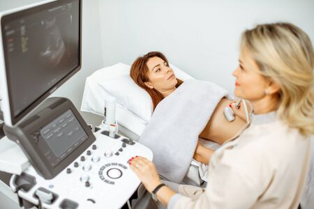 Female doctor performs ultrasound examination of a women's pelvic organs or diagnosing early pregnancy at the medical office Stock Photo