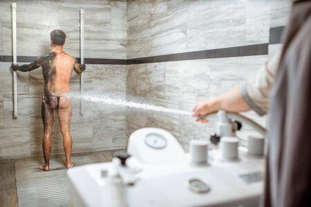 Mann mit Hochdruckdusche nach dem Schlammwickelverfahren im luxuriösen SPA-Salon. Konzept der Hydrotherapie und Sharko-Dusche
