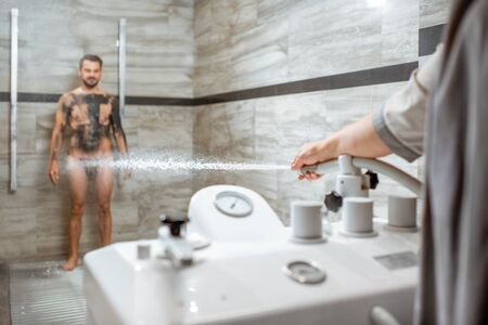 Man having high pressure shower after the mud wrapping procedure at the luxury SPA salon. Concept of hydrotherapy and Sharko shower