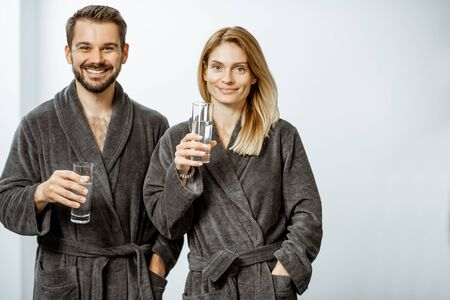 Portrait of a man and woman in bathrobes drinking mineral thermal water at the pump-room while resting at the luxury resort Stock Photo
