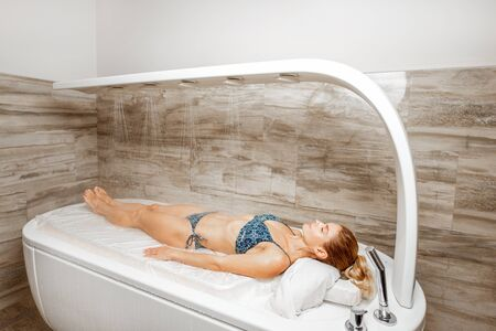 Beautiful woman in swimsuit lying on the wet bed under the hot shower, having a hydromassage in the spa salon