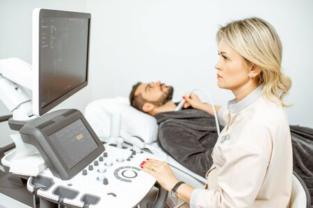 Female doctor performs ultrasound examination of a mens thyroid in the medical office. Concept of ultrasound diagnostics of male health 스톡 콘텐츠