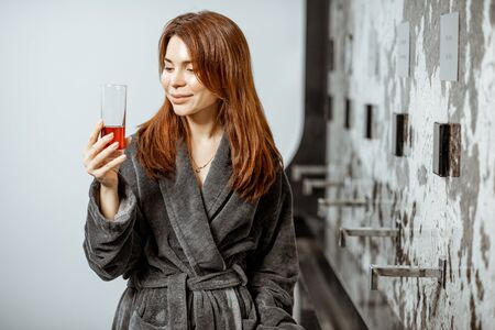 Beautiful woman in bathrobe drinking mineral water with wine extract at the pump-room while resting at the luxury resort Stok Fotoğraf