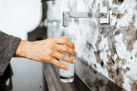 Pouring mineral thermal water into the drinking glass at the pump-room, close-up Stock Photo