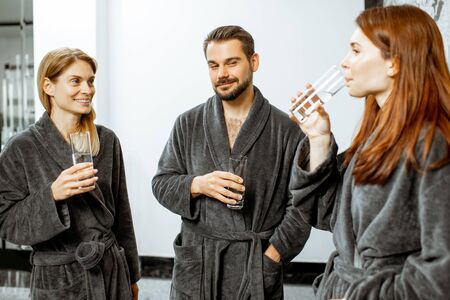 Group of people in bathrobes drinking mineral thermal water at the pump-room while resting at the luxury resort Stock Photo