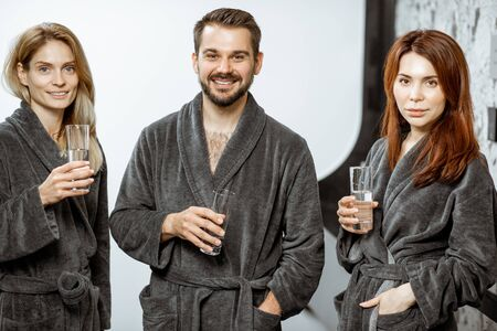 Portrait of a group of happy people in bathrobes drinking mineral thermal water at the pump-room while resting at the luxury resort