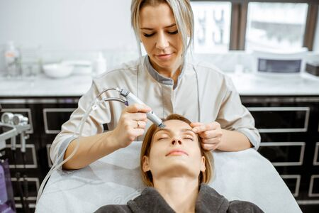 Cosmetologist making vacuum hydro peeling on the forehead region to a woman at the luxury beauty salon. Concept of a professional facial treatment