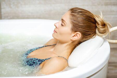 Schöne Frau, die sich in der Badewanne mit einer Hydromassage-Therapie im SPA entspannt