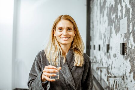 Portrait of a beautiful woman in bathrobe drinking mineral thermal water at the pump-room while resting at the luxury resort