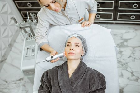 Female cosmetologist making oxygen mesotherapy to a woman at the luxury beauty salon. Concept of a professional facial treatment
