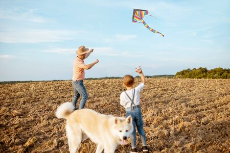 Father and son launching colorful air kite on the field, dog walking around. Concept of a happy family having fun during the summer activity Foto de archivo - 132049330