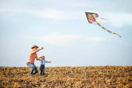 Father with son launching colorful air kite on the field. Concept of a happy family having fun during the summer activity Foto de archivo - 132049634