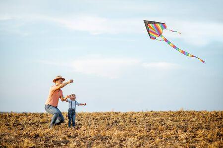 Padre con hijo lanzando cometas de aire colorido en el campo. Concepto de una familia feliz divirtiéndose durante la actividad de verano