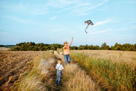 Father with son launching colorful air kite on the field, wide landscape view with copy space. Concept of a happy family having fun during the summer activity Foto de archivo - 132049200