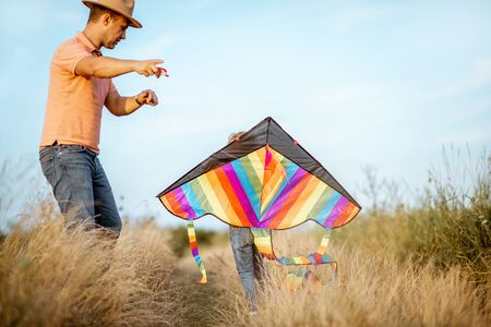Father with son launching colorful air kite on the field. Concept of a happy family having fun during the summer activity Zdjęcie Seryjne
