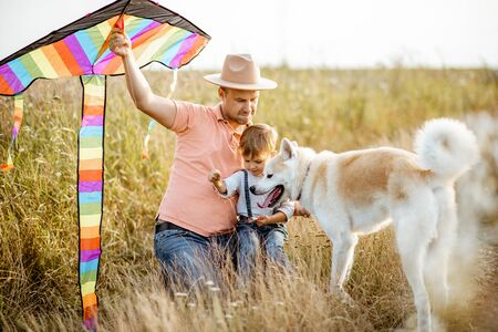 Portrait of a happy father and son holding colorful air kite while sitting together with dog on the field during the sunset